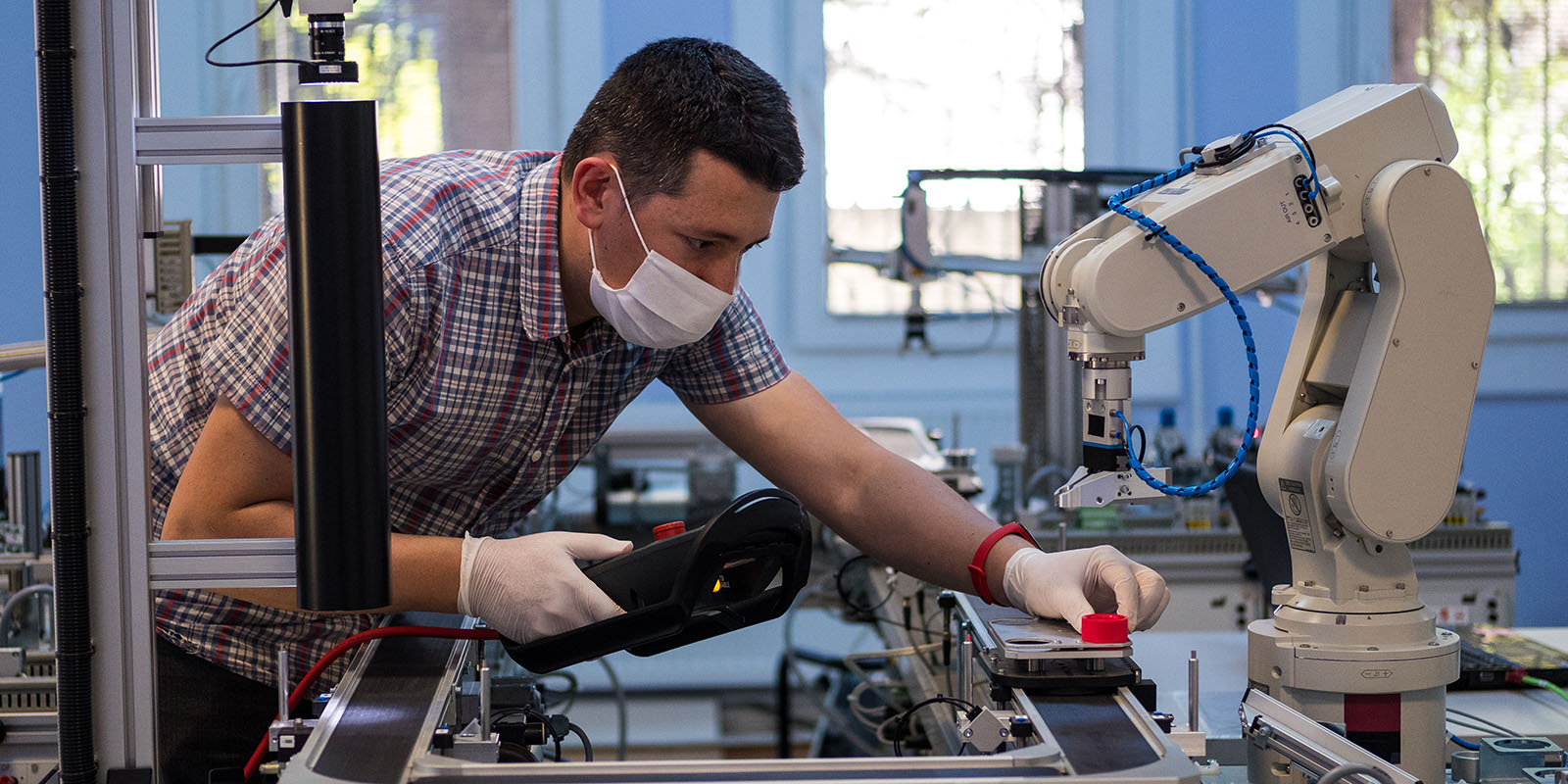 Man programming robot arm with teach pendant